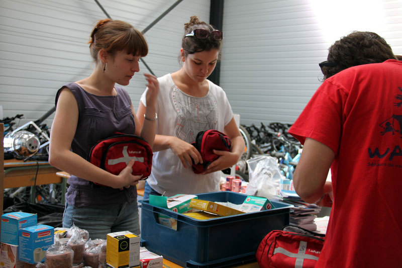 Maelenn, Camille et Johan s'affairent à préparer les malles qui équiperont les infirmeries de nos centres de vacances.